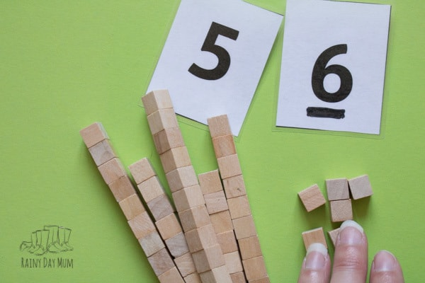 separating 56 into the 50s and 6s using place value wooden blocks made at home
