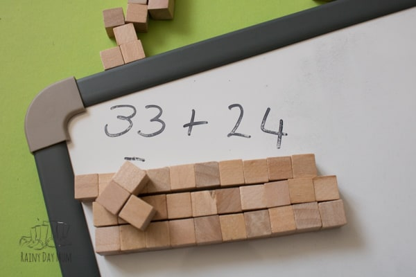 wooden homemade math manipulatives for addition and subtraction with a white board showing the sum 33+24=