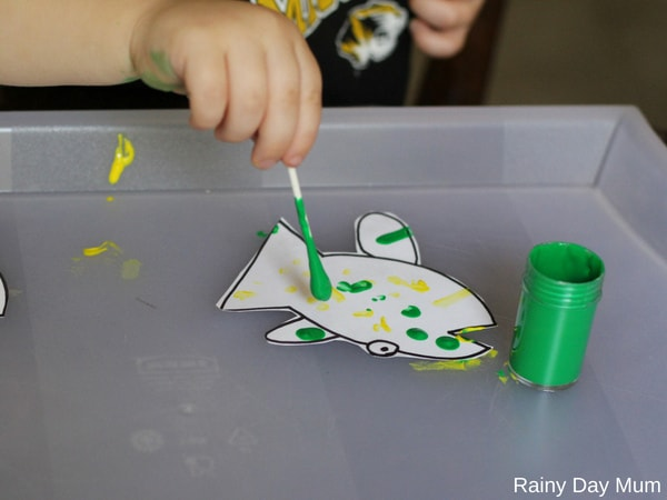 toddler using a qtip to colour in fish for a hands-on math pattern activity