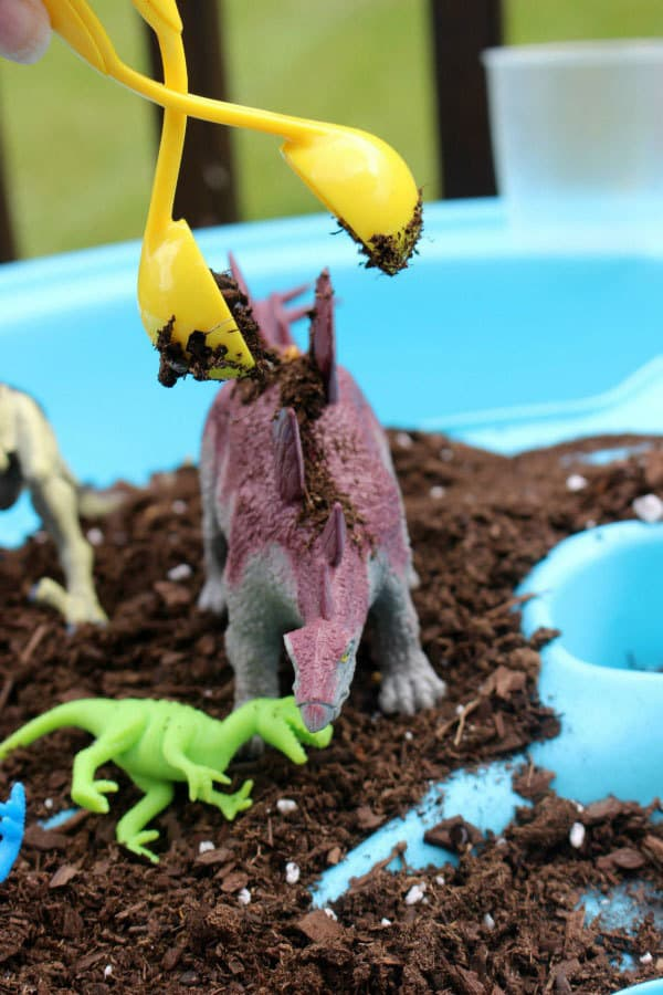 Scoop, pour, rinse, play with this sensory small world dinosaur activity in the water table for toddlers and preschoolers