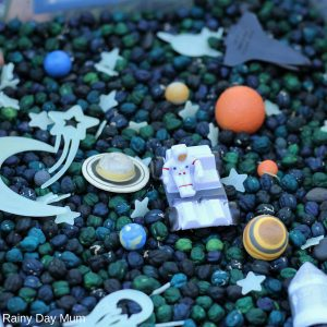 simple to set up space themed sensory bin for toddlers and preschoolers with dyed chick peas and glow in the dark stars