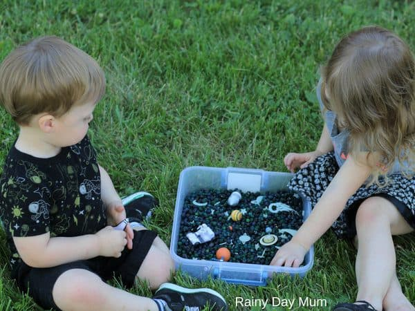 kids playing in the space themed sensory bin for the book There was an old martian who swallowed the moon outside on the grass