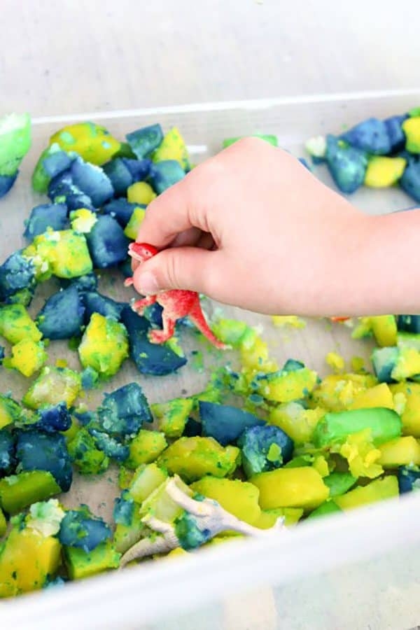 stomping and playing with the dinosaur sensory bin