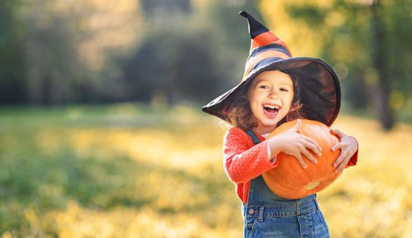 Little girl picking her own pumpkin for Halloween from the pumpkin patch