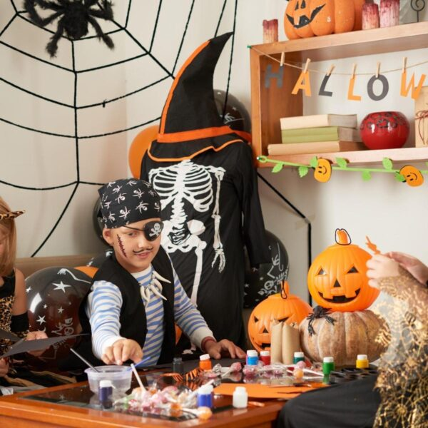 young child making halloween crafts at home