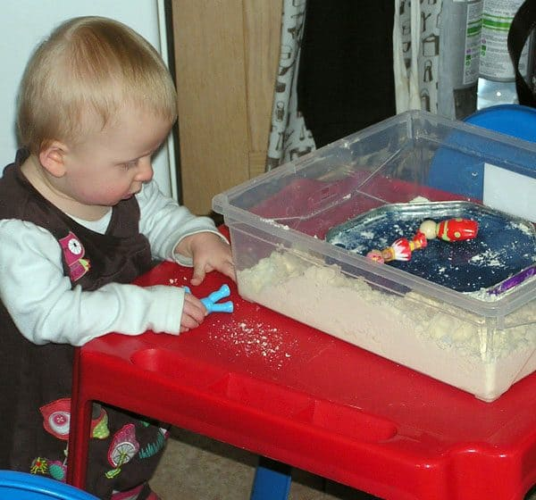 10-month-old baby girl playing in a sensory bin standing up