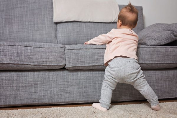 9-month-old baby girl cruising around the furniture at home