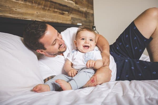 dad and 9-month-old baby singing together on the bed having fun