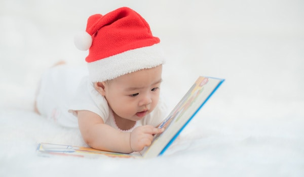 Baby reading a Christmas Board Book in a Santa Hat