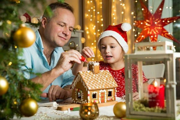 Father and Daughter building a Gingerbread House Together
