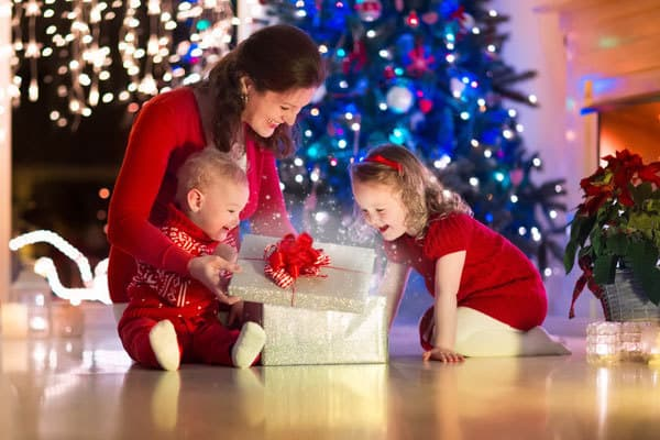 Family opening a Christmas Eve Box in front of a Christmas Tree