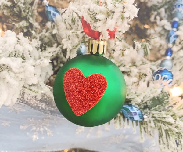 grinch heart ornament to make with kids hanging on a white christmas tree