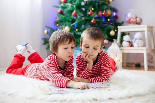 kids reading a christmas picture book on a fur rug infront of a christmas tree at home.