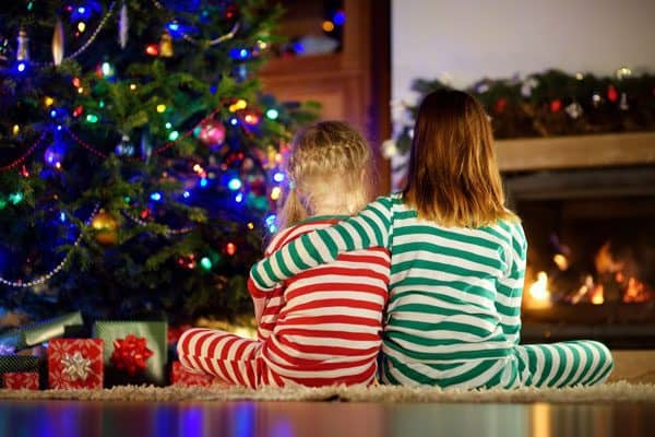 kids sitting infront of the Christmas tree on christmas eve in Christmas pyjamas