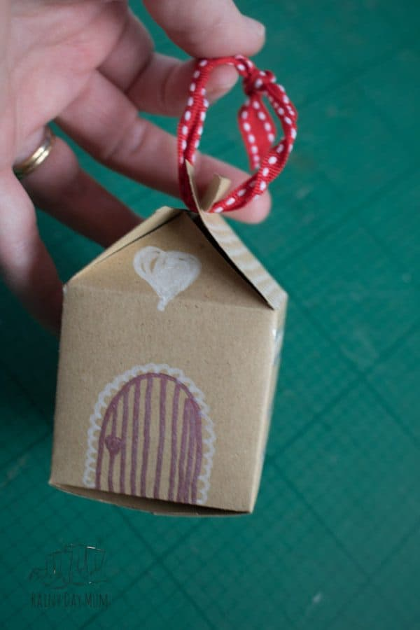 ribbon attached to hang kids craft gingerbread house box on the christmas tree