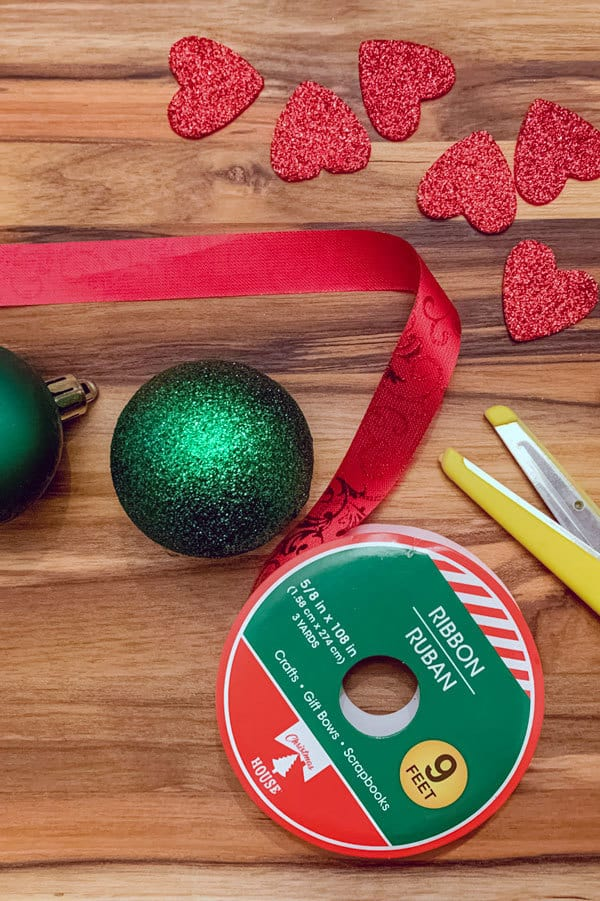 toddler crafting supplies to create some simple grinch ornaments pictured as a flat lay