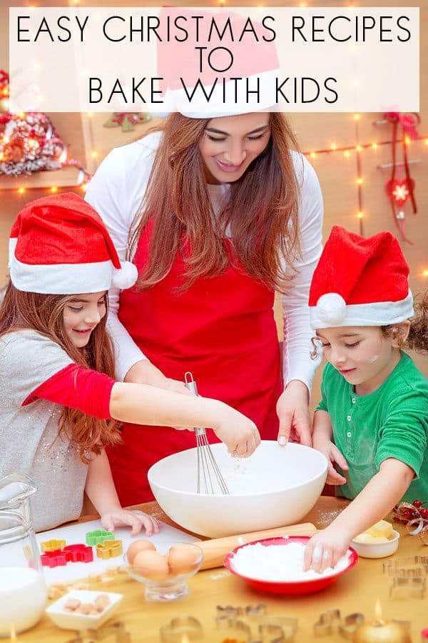 Christmas recipes to cook with toddlers - a picture of mum and kids cooking together wearing santa hats