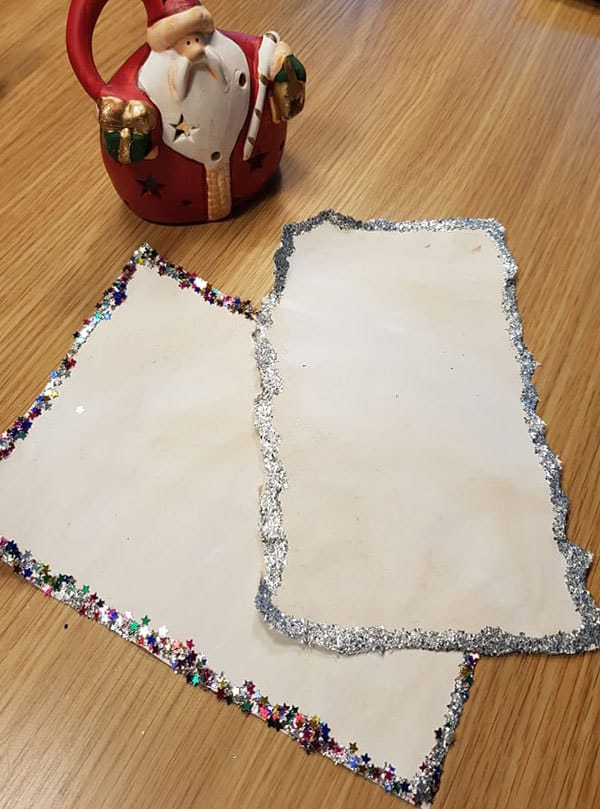 Adding details to Christmas letters with glitter and stars and sparkles