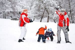 family having fun together in the winter with a simple winter activity snowball fights