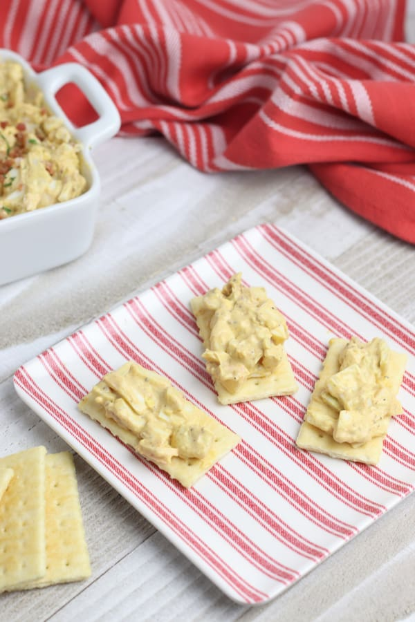 Egg salad on crackers with bacon sprinkled on top