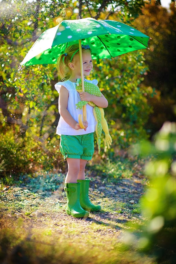 girl holding toy frog in spring under an umbrella
