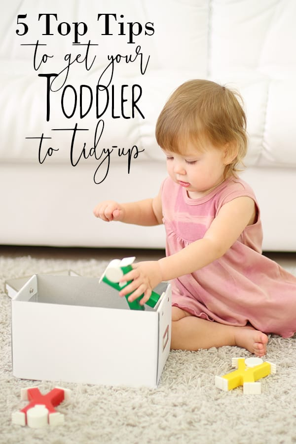 toddler tidying up toys into a box with 5 top tips to get them to help
