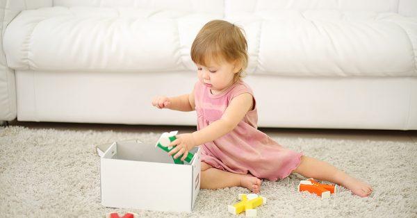 toddler helping put toys away