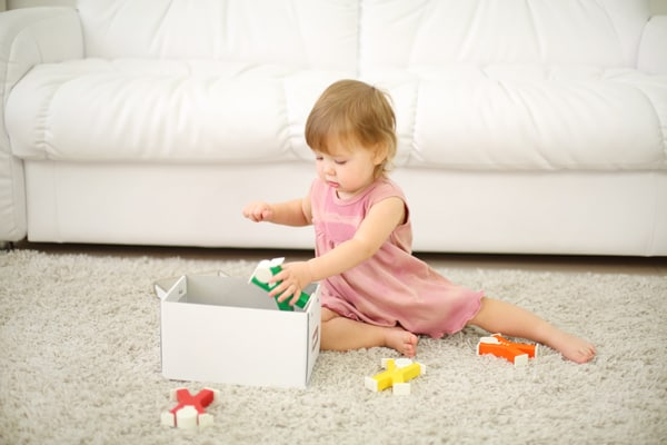 toddler putting toys away in a box