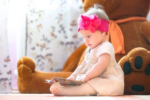 10 Month old baby girl reading a board book with a big teddy bear