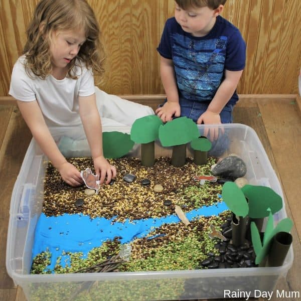 Preschooler and toddler playing in a sensory bin inspired by The Gruffalo