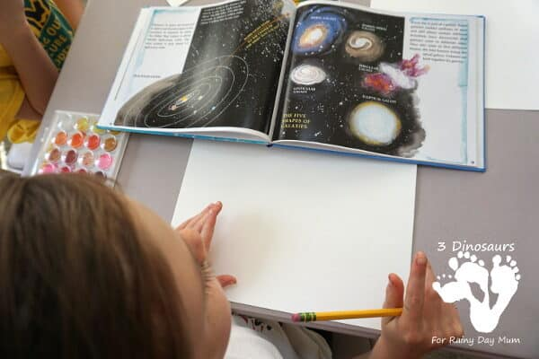 Child using a non-fiction book for inspiration to create Galaxy theme Art work