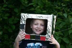 Child wearing space helmet they have made with simple materials in the junk model box