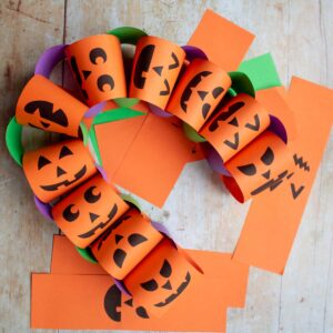 homemade halloween paper chains with free printable jack-o-lantern faces to make with kids