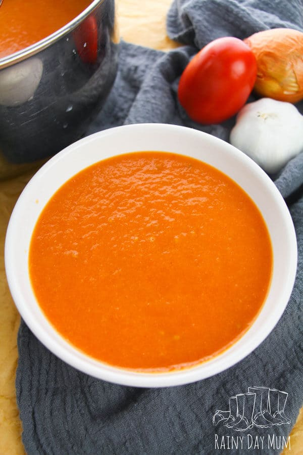 tomato soup in a white bowl with ingredients beside