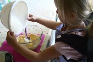 preschooler measuring and pouring whilst making cookies