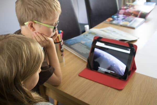 kids researcing a science topic using YouTube Videos and making notes