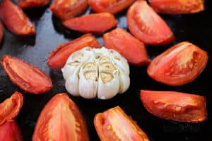 roasted plum tomatoes and garlic on a roasting tin