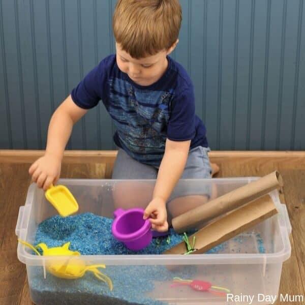 toddler playing in a nursery rhyme themed sensory bin
