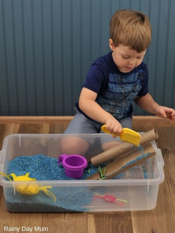 down came the rain - pouring blue rice down an pretend water spout for an Incy Wincy Spider Sensory Bin