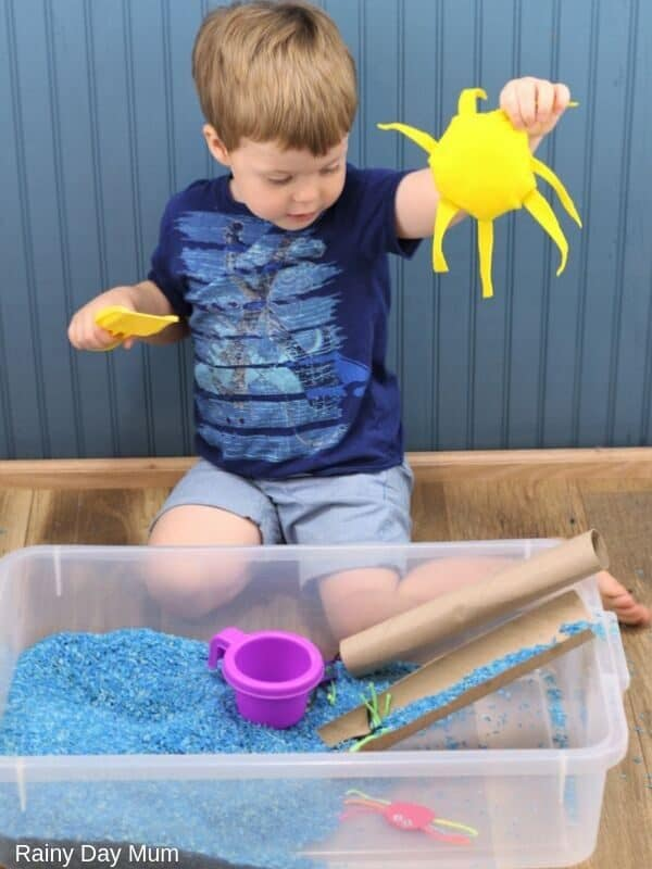 Toddler holding up a felt sun for the sun coming out in the rhyme Itsy Bitsy Spider