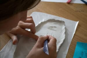 child engraving cartouches onto air drying clay for a Egyptian history project