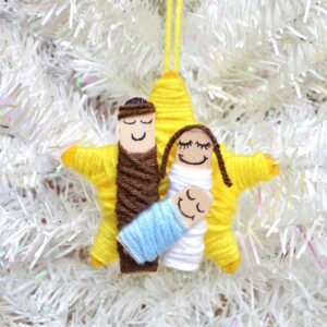 Nativity Story Ornament Craft for Kids to Make with Craft Sticks and Yarn displayed on a white Christmas Tree