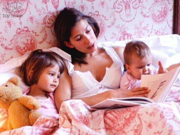 reading in bed to a toddler and a baby part of a great bedtime routine you can start from the beginning