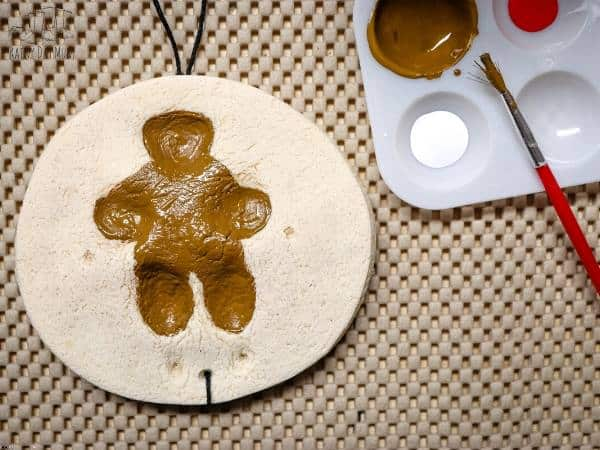 creating paw print decorations out of a salt dough and painting with kids for Christmas