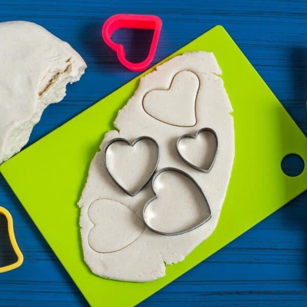Salt dough with hearts cut out on a green chopping board