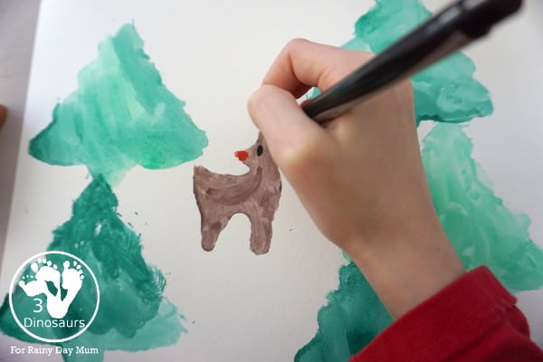 adding details to a christmas rudolph painting with marker pens