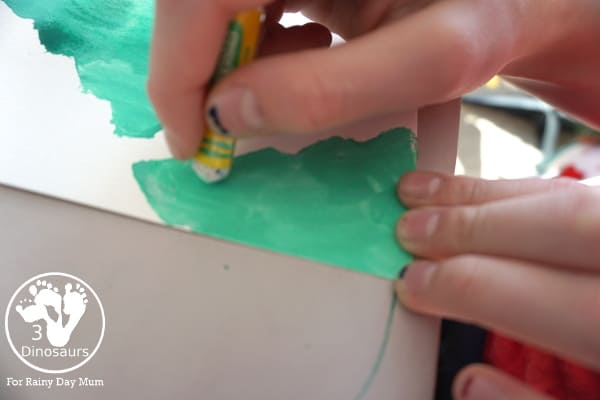 adding snow to a christmas painting with oil pastels