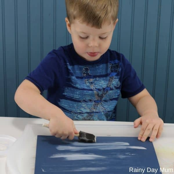 Toddler making the background of a winter art project for kids