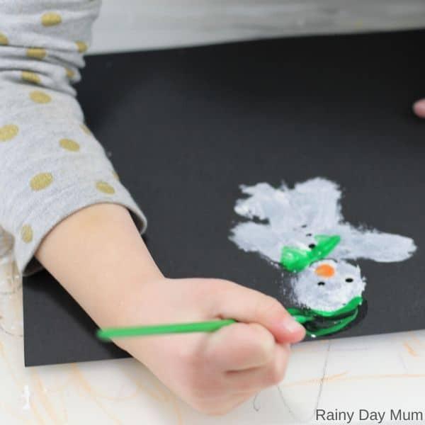 Kindgarten student painting a snowman picture