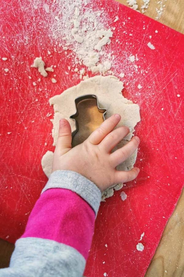 child making decorations with a cookie cutter